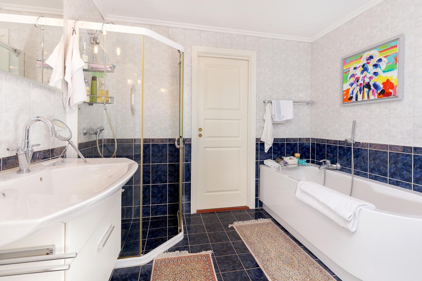 stort-fliselagt-bad-med-badekar-dusjkabinett-og-varmekabler