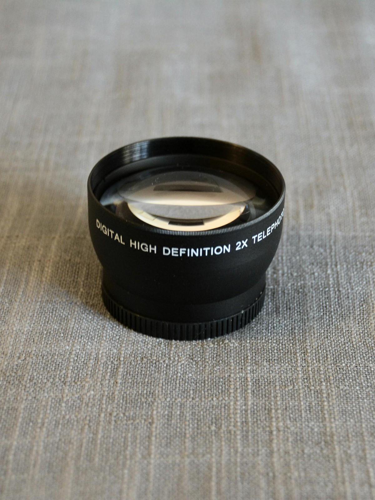 High Definition 2X Telephoto Lens (52mm) - Halden  - High Definition 2X Telephoto Lens. Passer til objektiver med 52mm filterstørrelse. Dette er en avtagbar linse som skrues på et eksisterende objektiv og dobler objektivets brennvidde optisk. MACRO for ekstreme nærbilder.  Linsen er sort og av - Halden