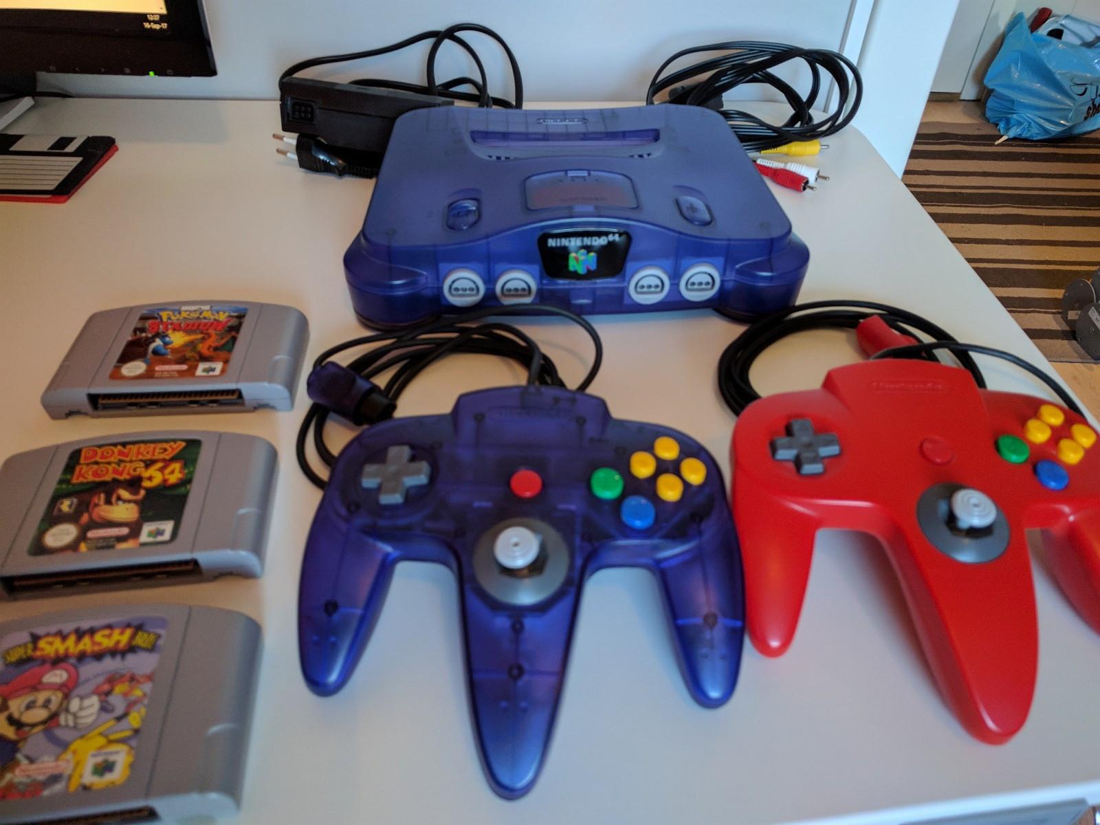 Nintendo 64 - blå/lilla - Oslo  - Nintendo 64 spillkonsoll i blå/lilla gjennomsiktig versjon selges med tilhørende kabler og utstyr. Alt er originalt fra Nintendo. - 1x Nintendo 64 lilla gjennomsiktig spillkonsoll - 2x kontrollere (en rød og en lilla gjennomsiktig)&#1 - Oslo