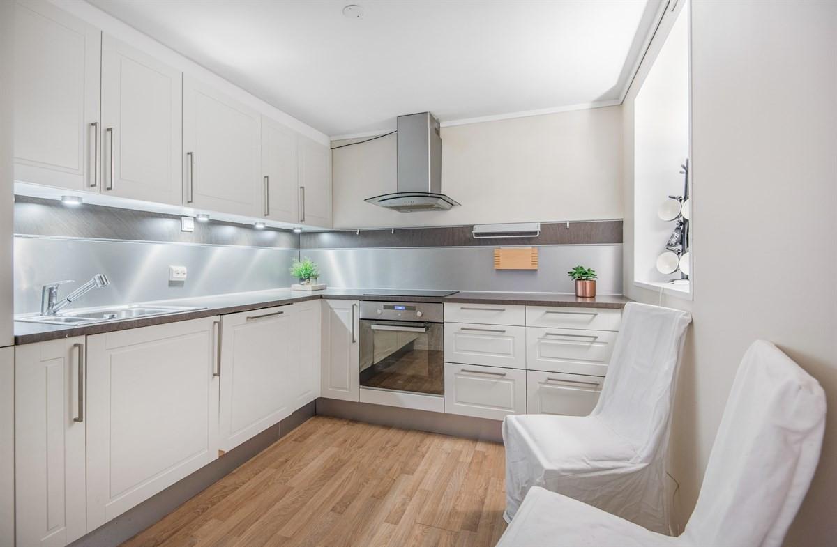 Kjøkken med nyere innredning med laminat benkeplate og integrerte hvitevarer.