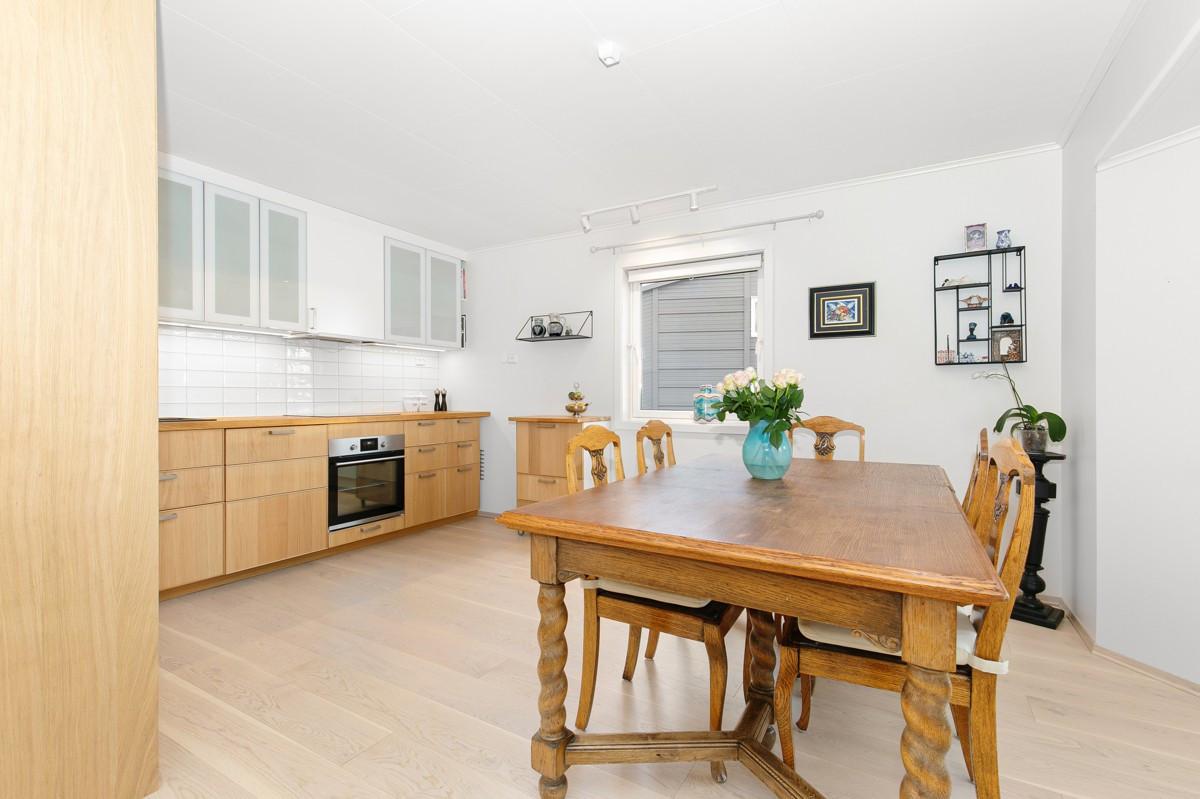 Kjøkken med integrerte hvitevarer og god plass til spisegruppe