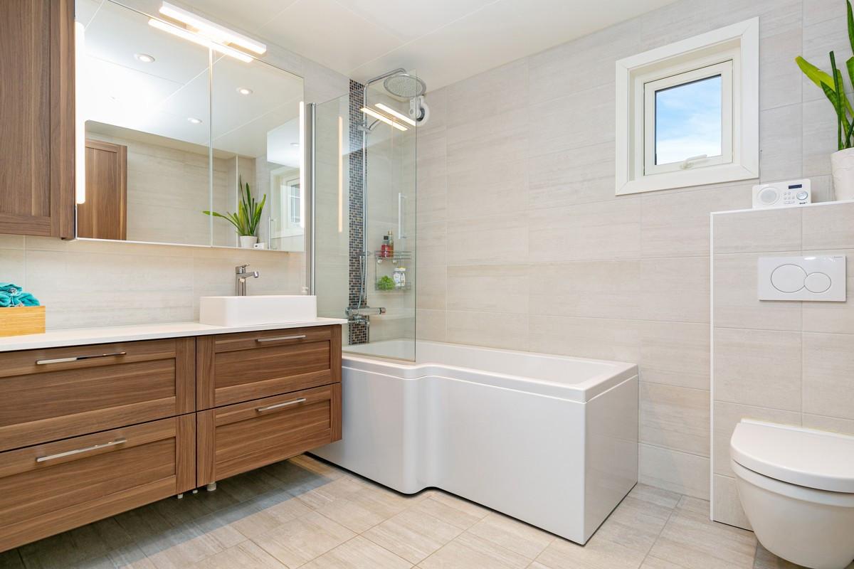 Fliselagt baderom med vegghengt wc, høyskap og godt med skuffeoppbevaring