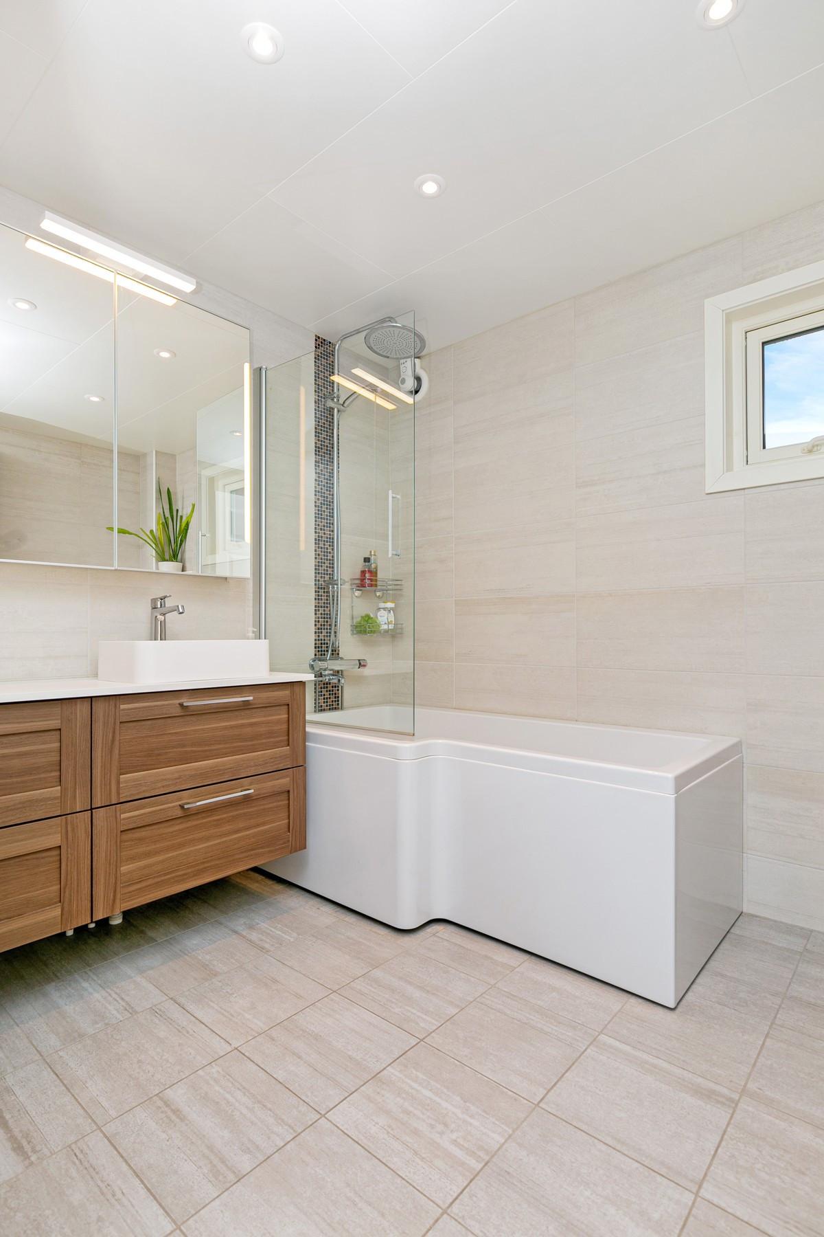 Badet er bygget med dusjhjørne under badekaret, slik at man enkelt kan fjerne badekaret å sette opp vanlige dusjdører