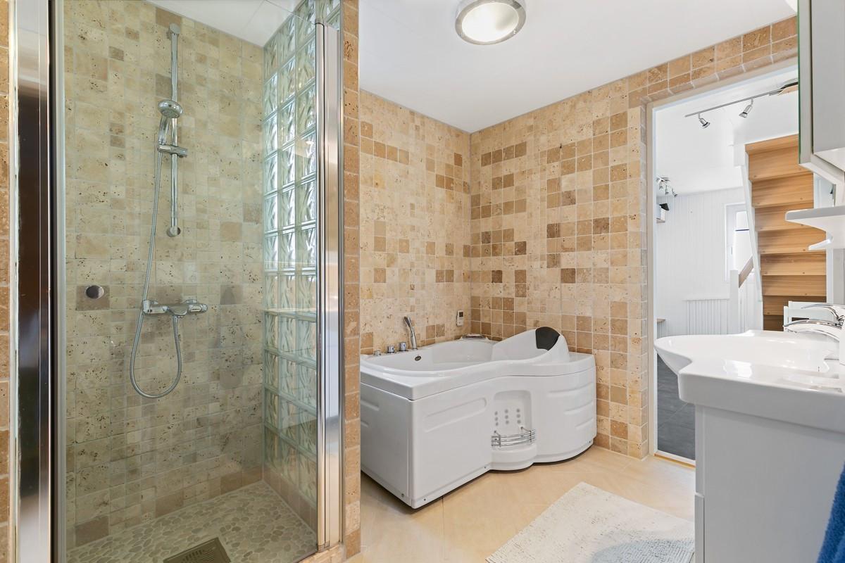 Komplett fliselagt baderom i 1. etasje med dusj, badekar og wc