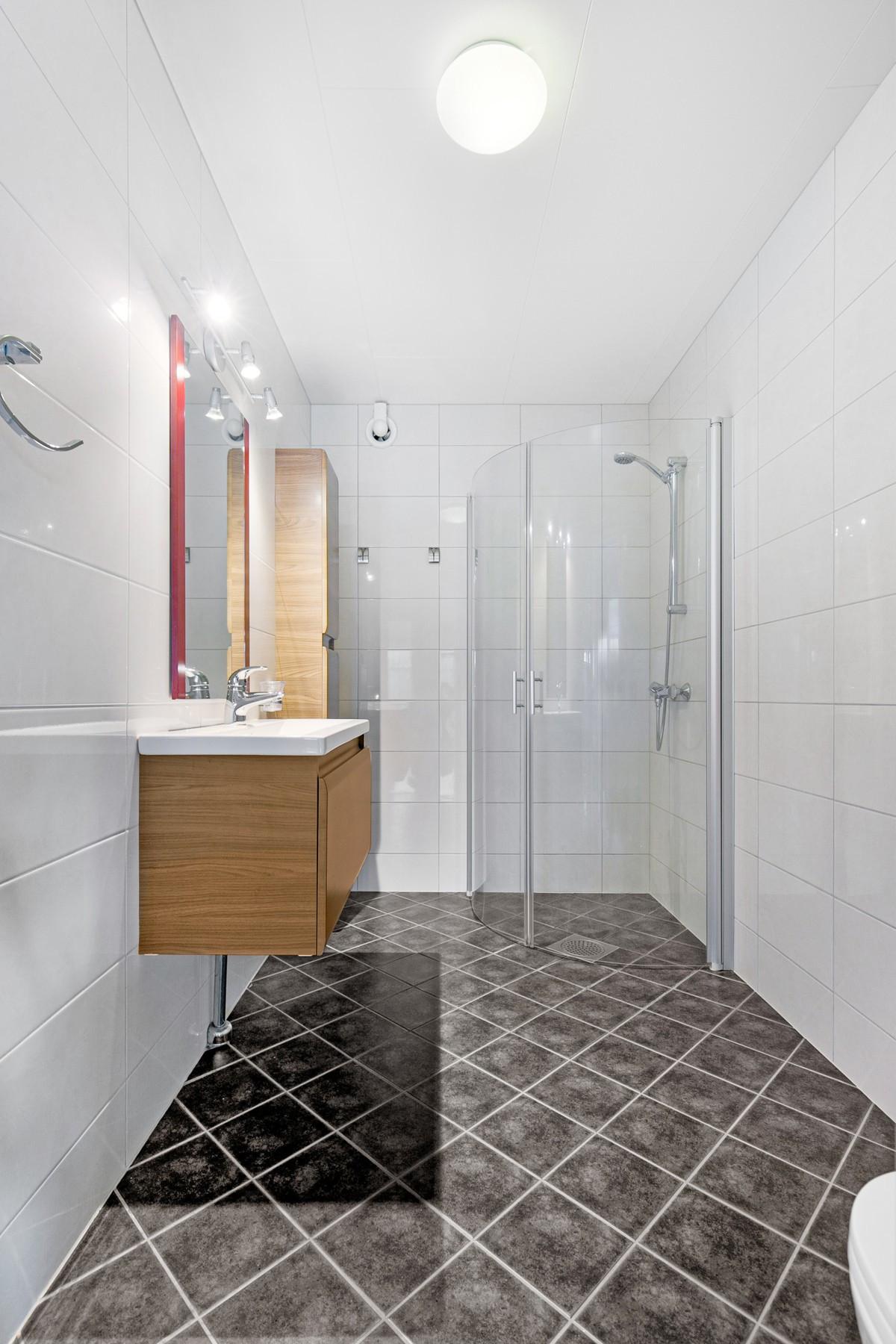 Komplett fliselagt baderom med dusjhjørne, baderomsinnredning og vegghengt toalett