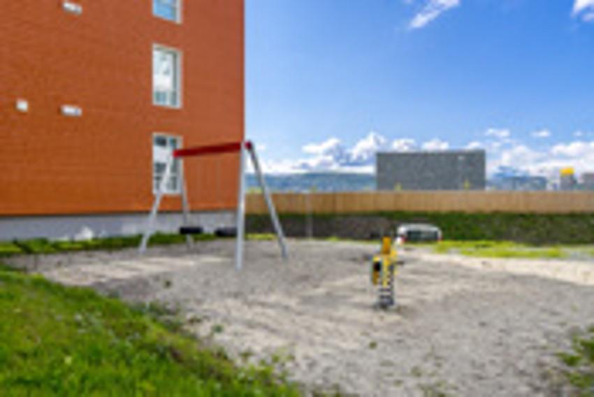 Fint lekeområde med ulike lekeapparater nedenfor boligblokken
