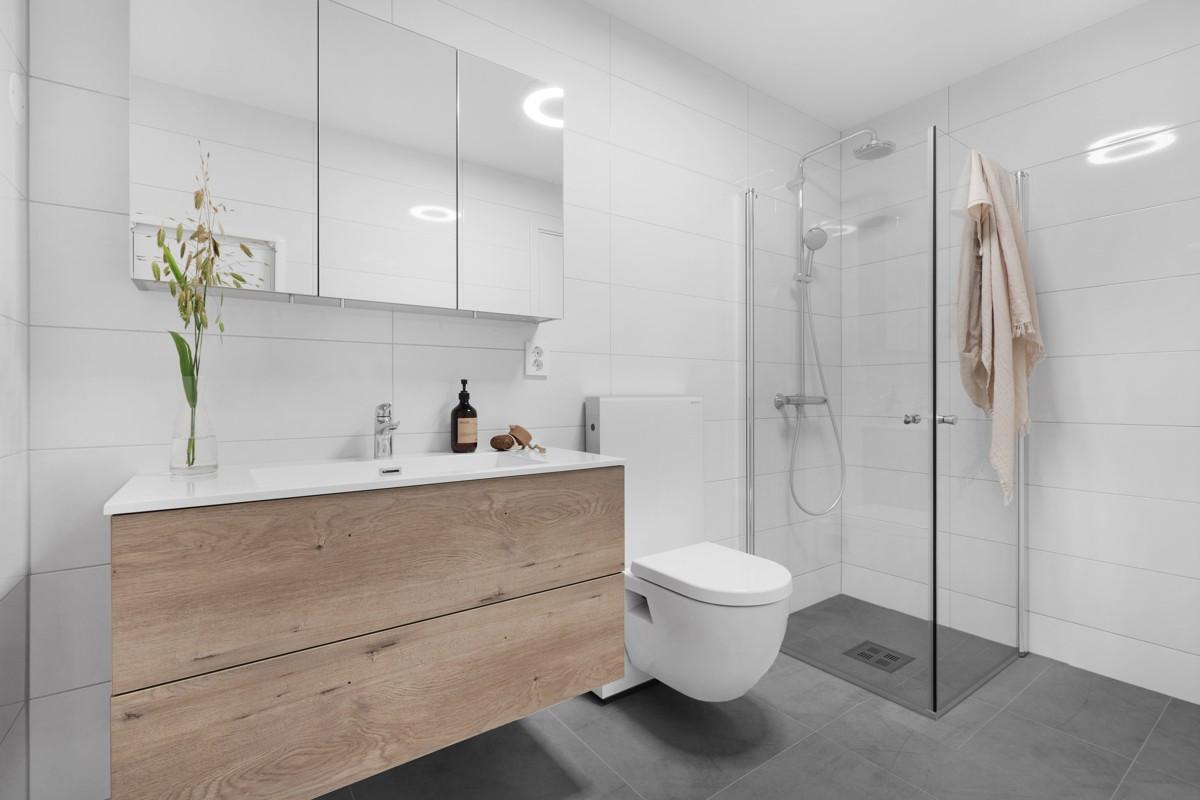 Baderom med dusshjørne og vegghengt wc