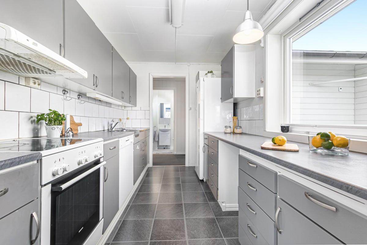 Kjøkken med god lagringsplass i over og underskap, dobbel oppvaskkum og flislagt vegg over benkeplate av laminat