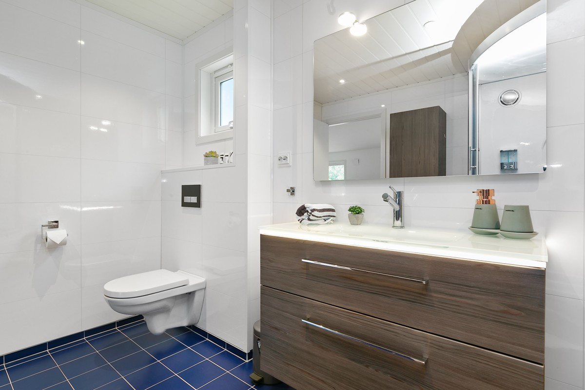 Renovert baderom med moderne servant, vegghengt wc og spotter i tak