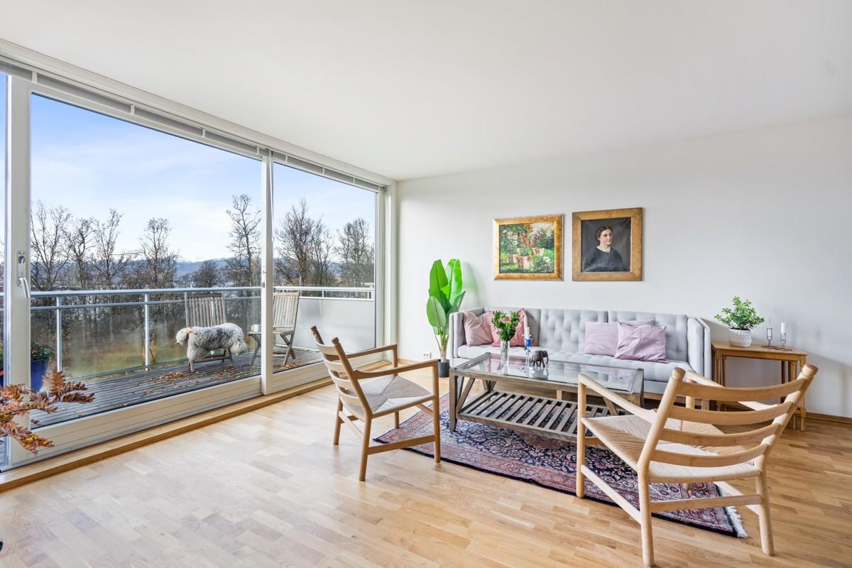 Lys og lekker stue med store vindusflater, rikelig med lysinnslipp og ingen innsyn