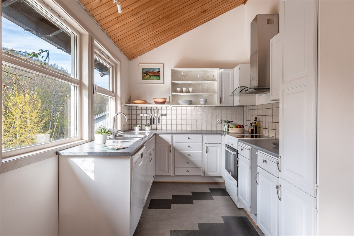 Kjøkkenet er lys og trivelig med vindu over benk