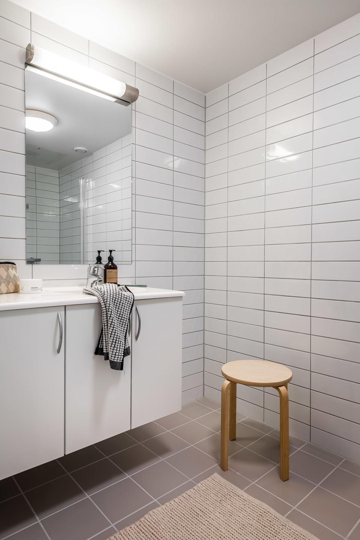 Komplett fliselagt baderom med moderne baderomsinnredning, samt speil og belysning
