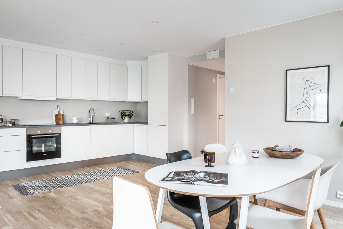 Kjøkkeninnredning med hvite glatte fronter, samt integrerte hvitevarer