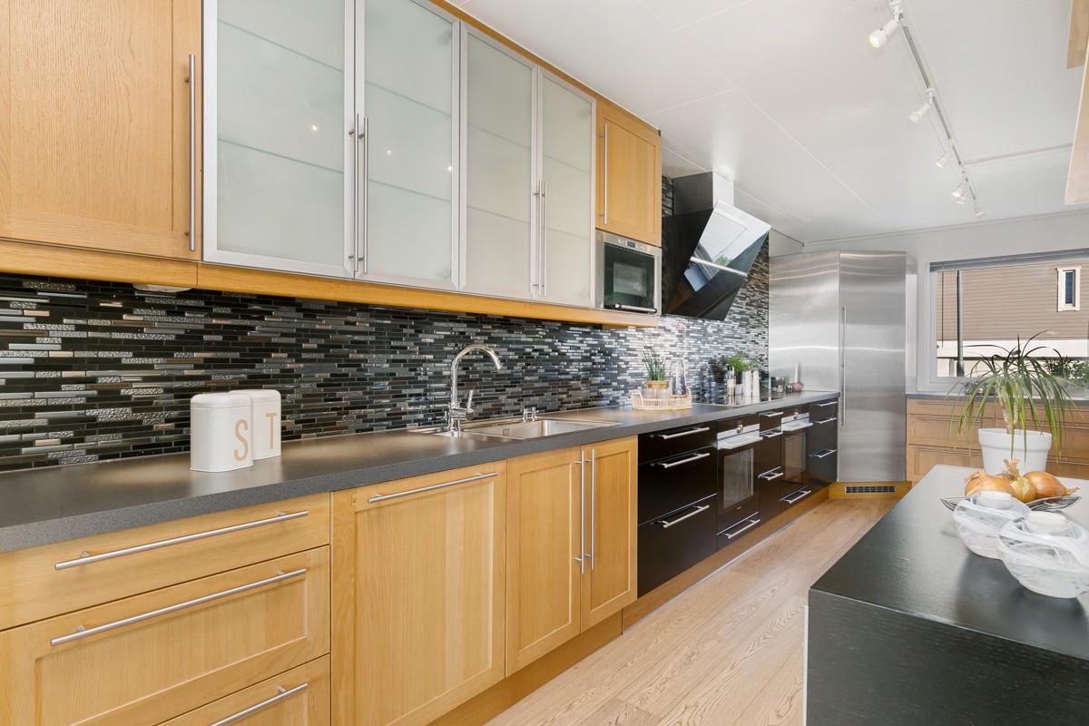 Kjøkken med fronter av eik og stilfulle fliser over benk