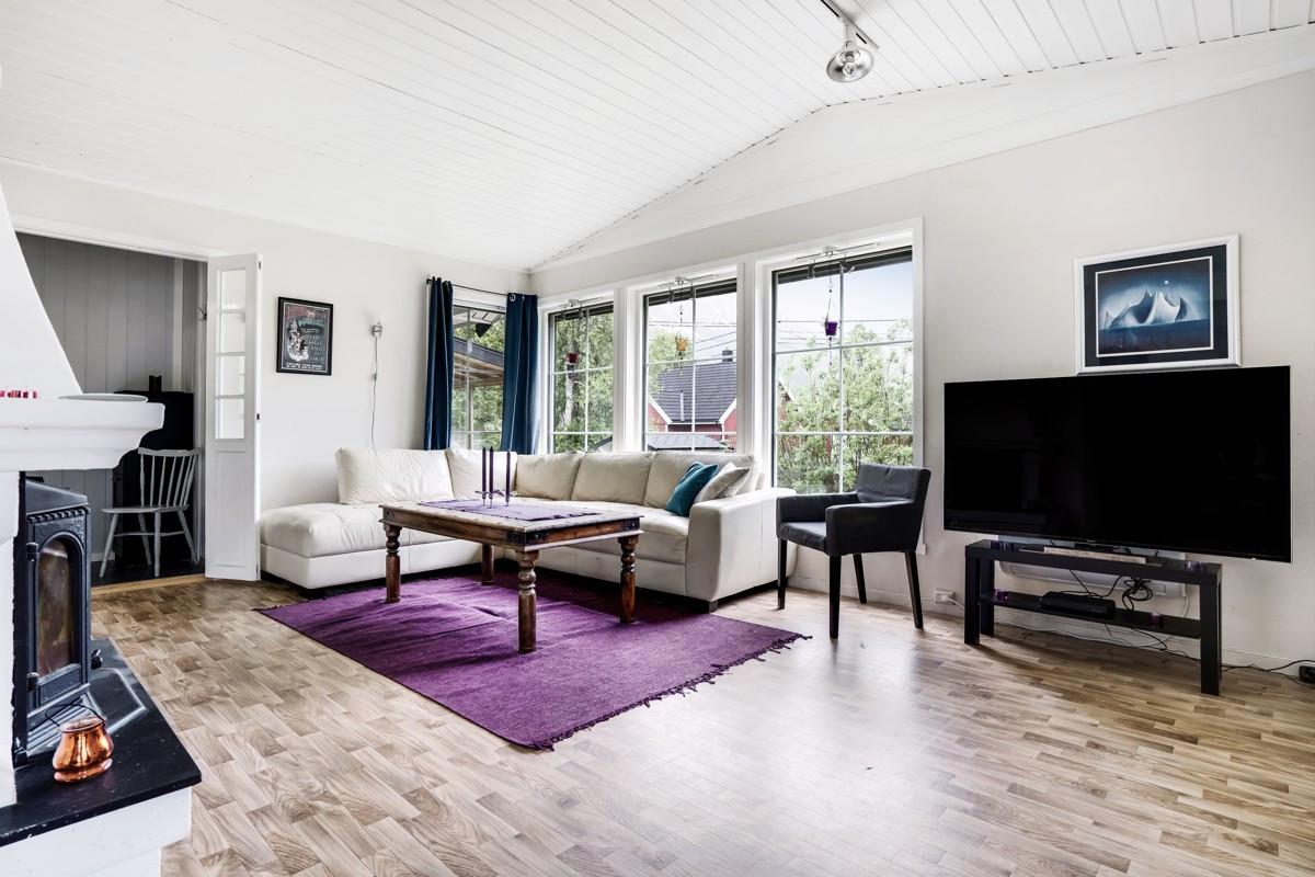 Romslig stue med store vindusflater
