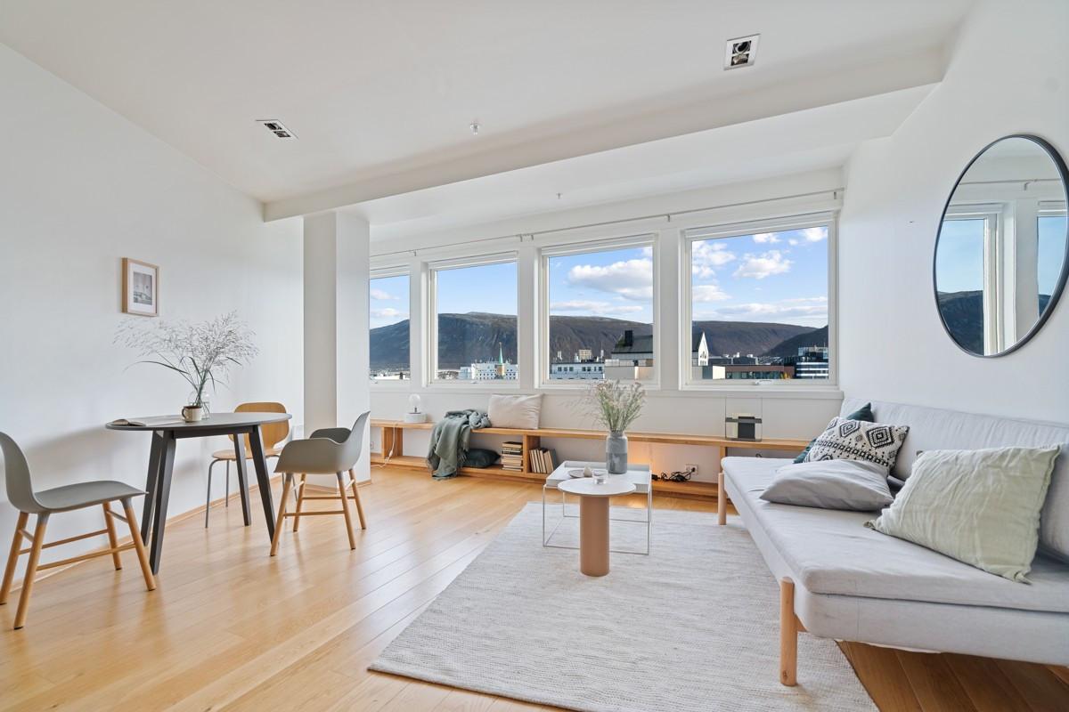 Stue og kjøkken i åpen løsning med glatte hvite fronter