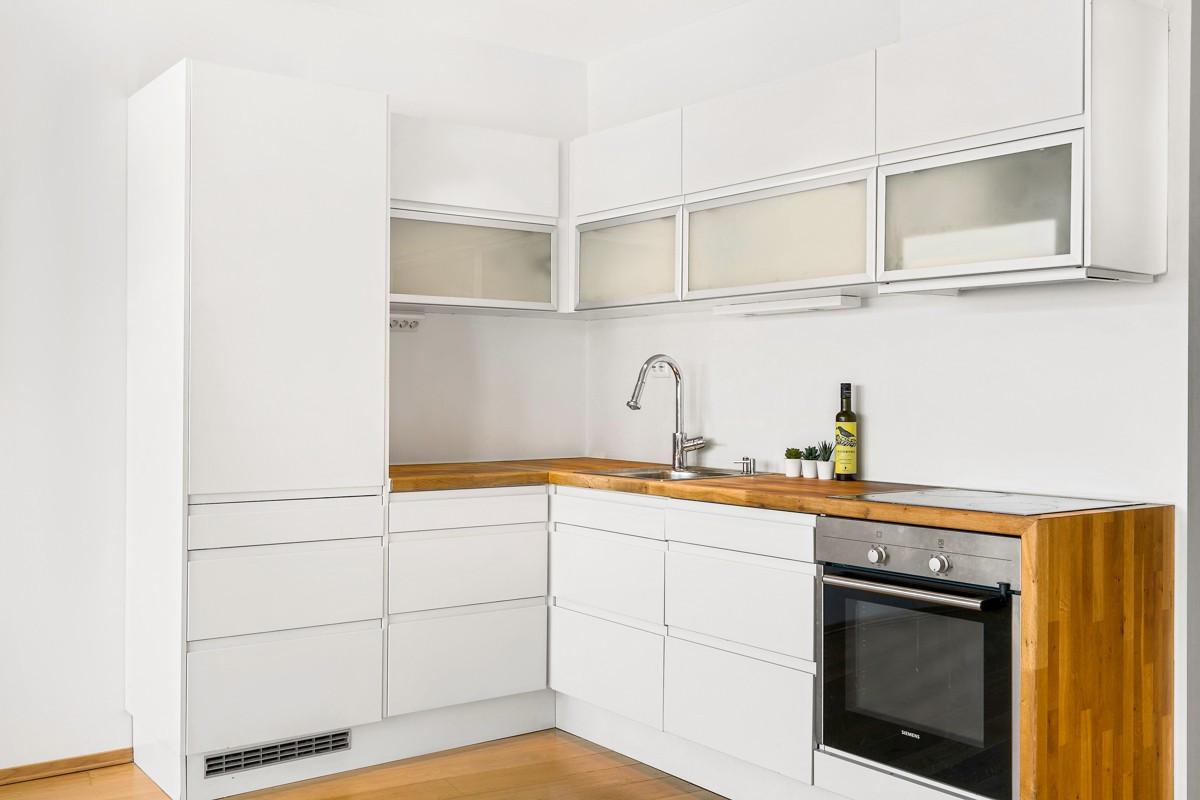 Kjøkkenet har integrerte hvitevarer og waterfall edge som gir leiligheten særpreg