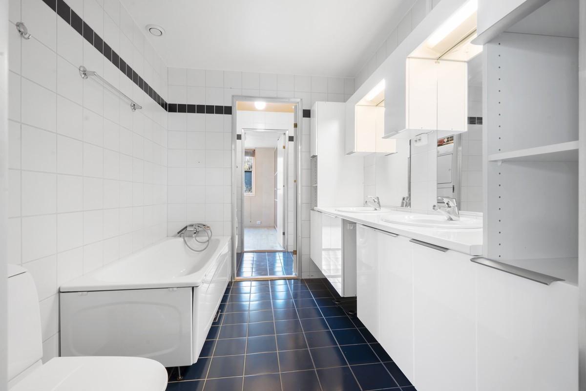 Komplett fliselagt baderom med badekar og dobbel servant