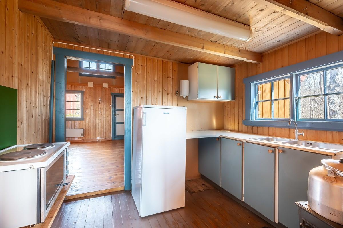 Kjøkken med enkel kjøkkeninnredning og oppvaskkum