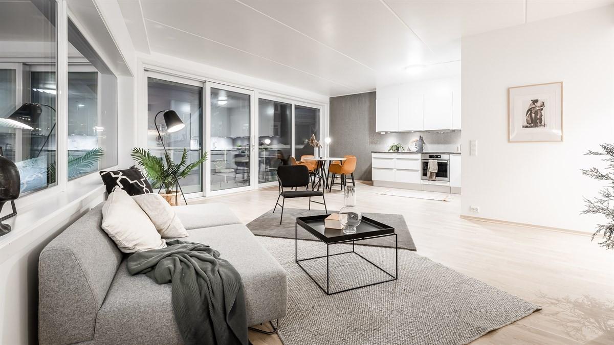 Romslig stue med parkett på gulv og lyse flater