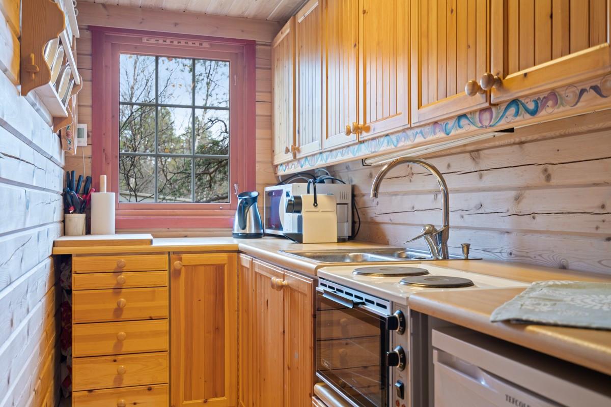 Kjøkken med profilerte fronter, vindu over benk og rom for komfyr, kjøl, mv.