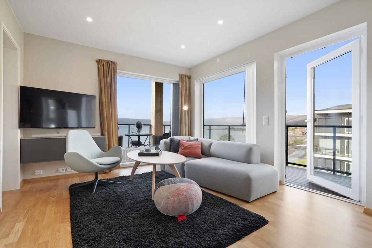 Stuen har store vindusflater med svært gode lysforhold og utgang til takoverbygd balkong