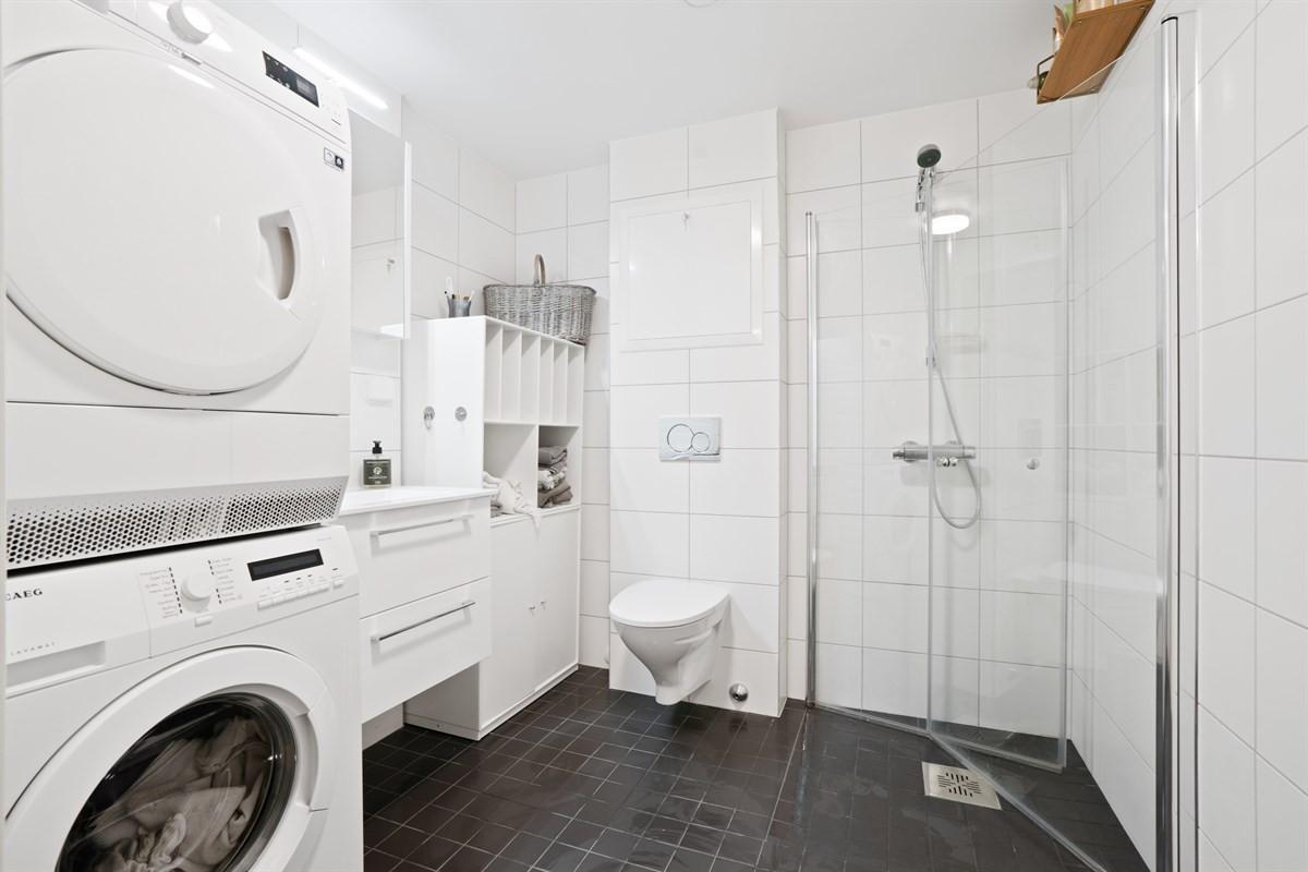 Fliselagt baderom med gulvvarme, dusjhjørne, servant og vegghengt wc