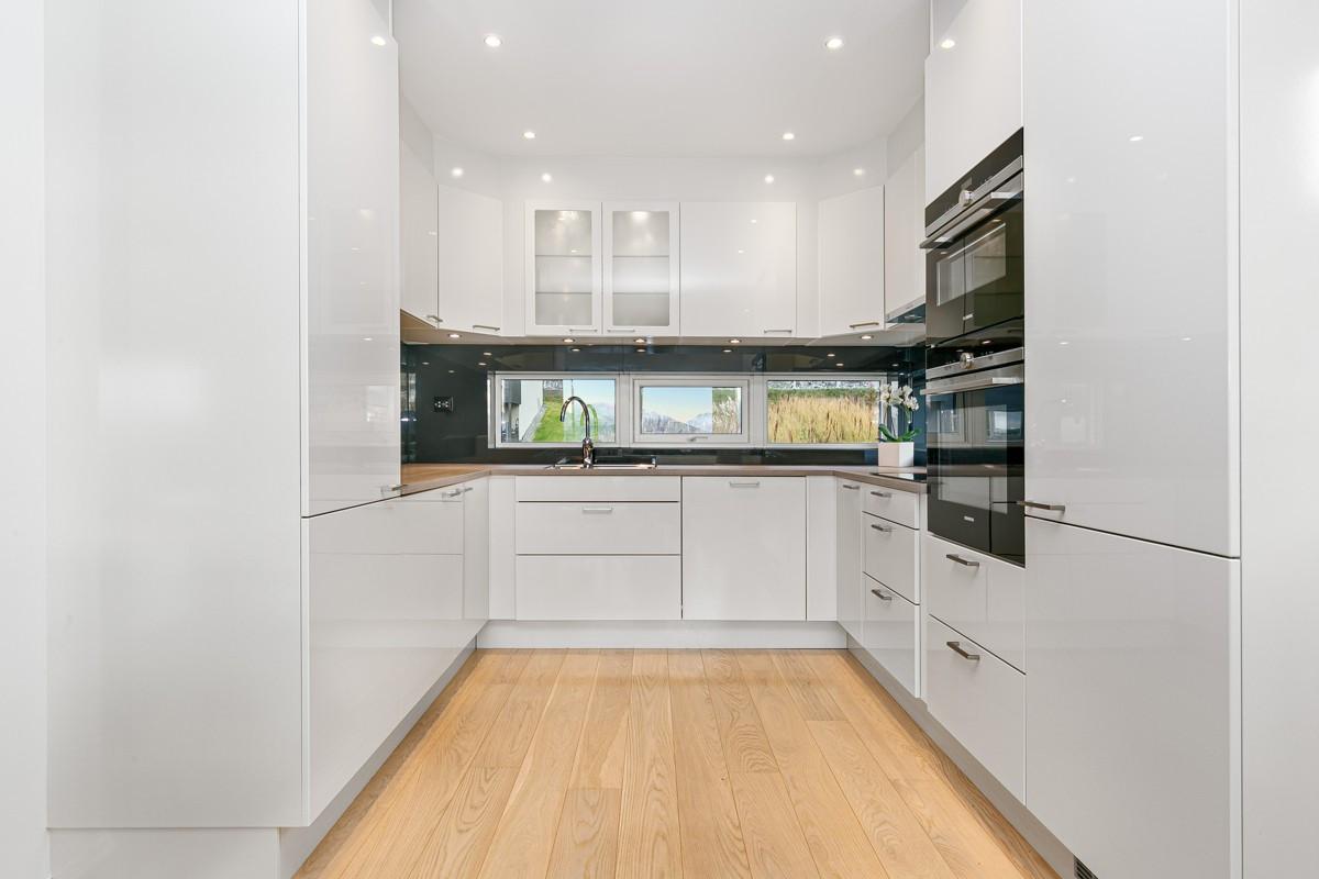 Moderne kjøkkeninnredning med hvite glatte fronter. Gode oppbevaringsmuligheter i over- og underskap, samt god benkeplass