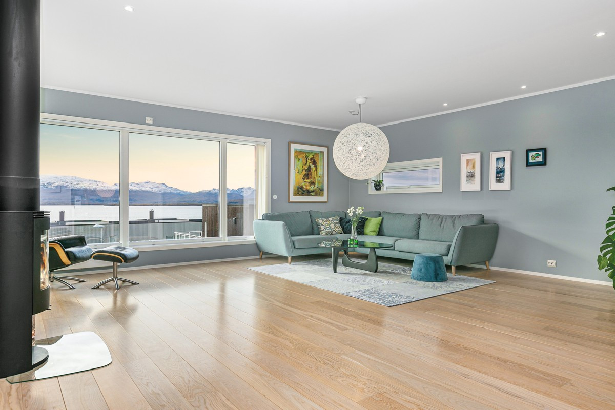 Romslig og åpen stue med store vindusflater og fantastisk utsikt