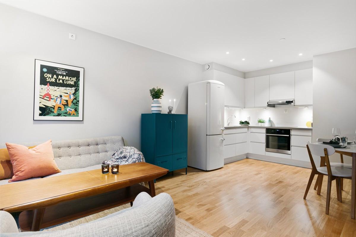 Parkett på gulv og spotter i tak i stue/kjøkken - spotter i børstet stål med dimmer er gjort som tilvalg i både kjøkken og stue og gir leiligheten en lun atmosfære