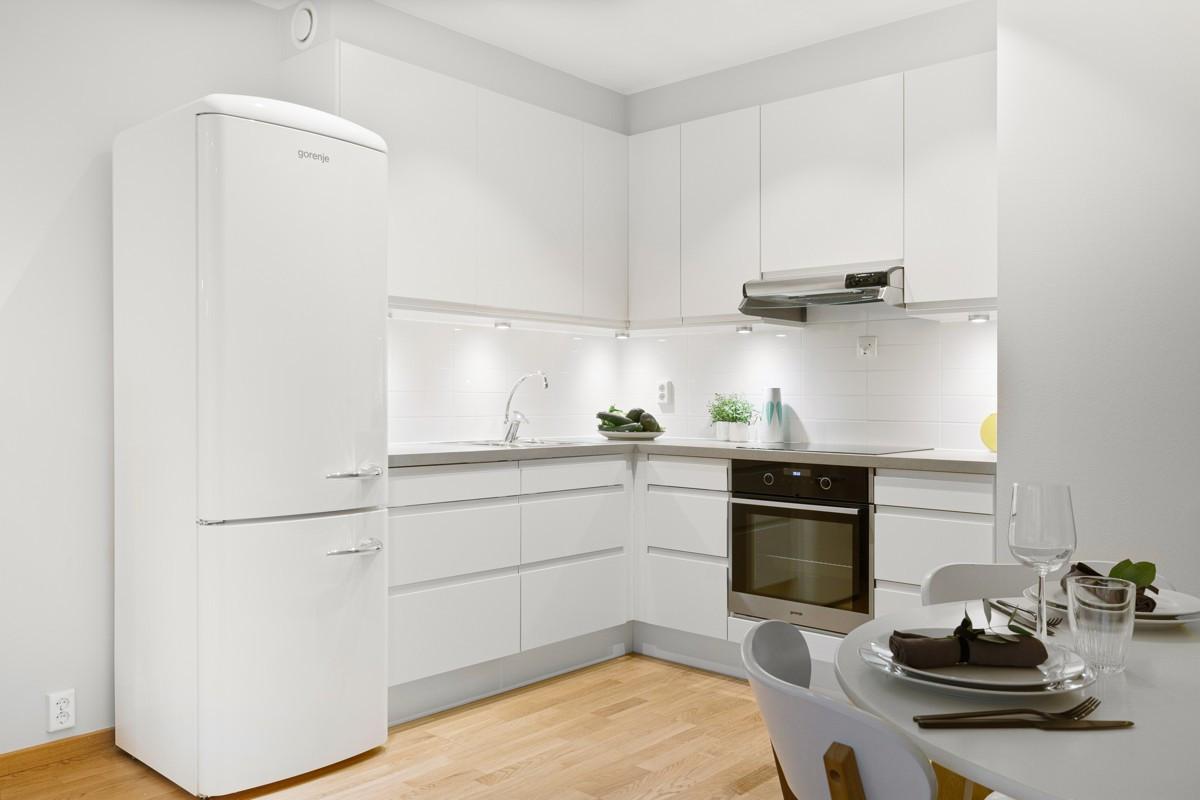 Stilrent kjøkken med lekre tilvalg som takhøye skap, integrerte hvitevarer, særegne fliser bak benk og grå benkeplate