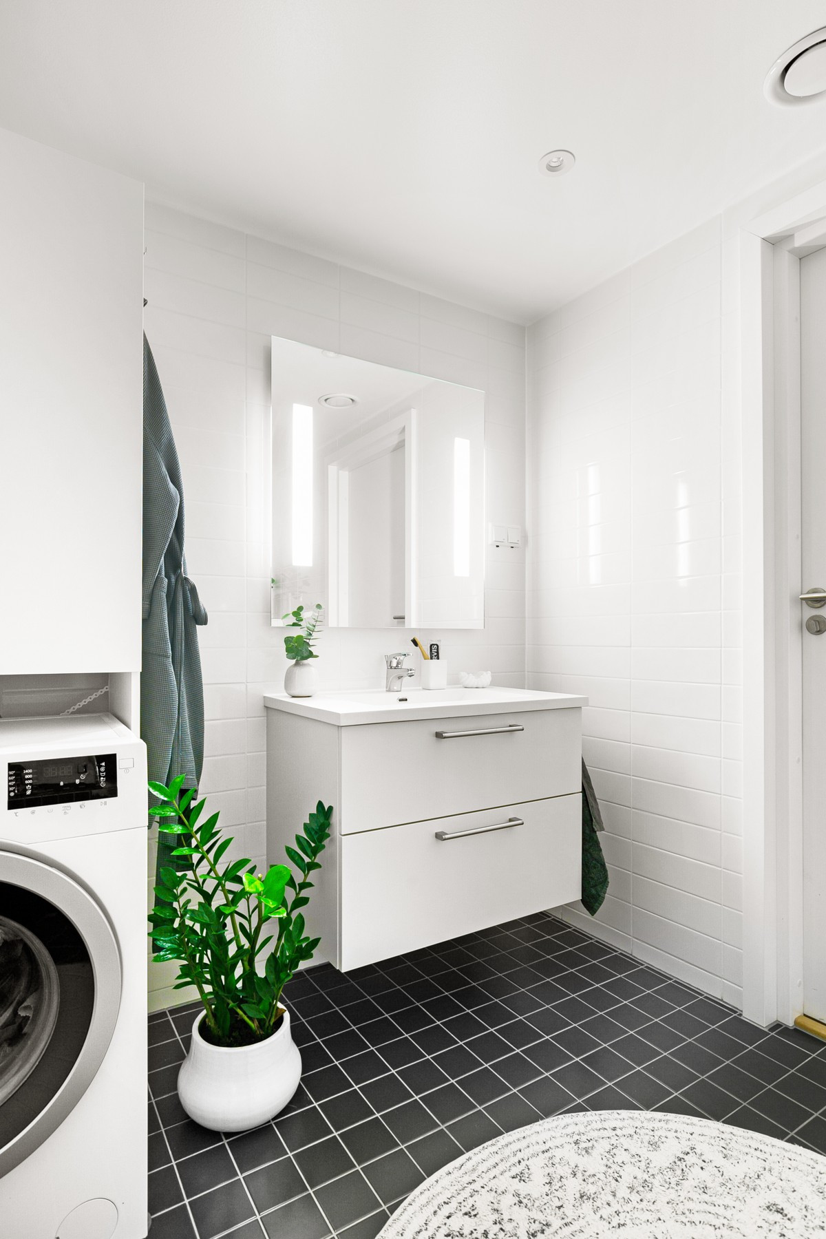 Servant og speil med lys - det er gjort tilvalg for særegne fliser som gir badet en pen finish