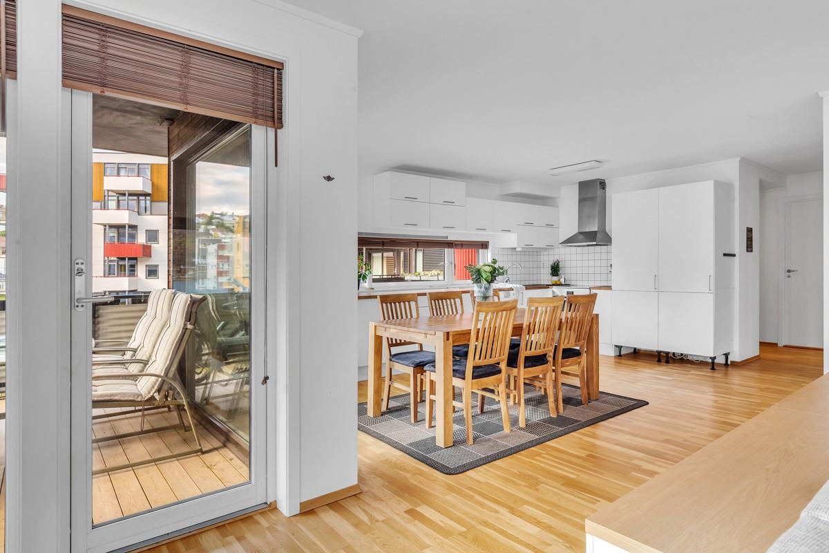 God plass til stort spisebord i åpen stue- kjøkkenløsning