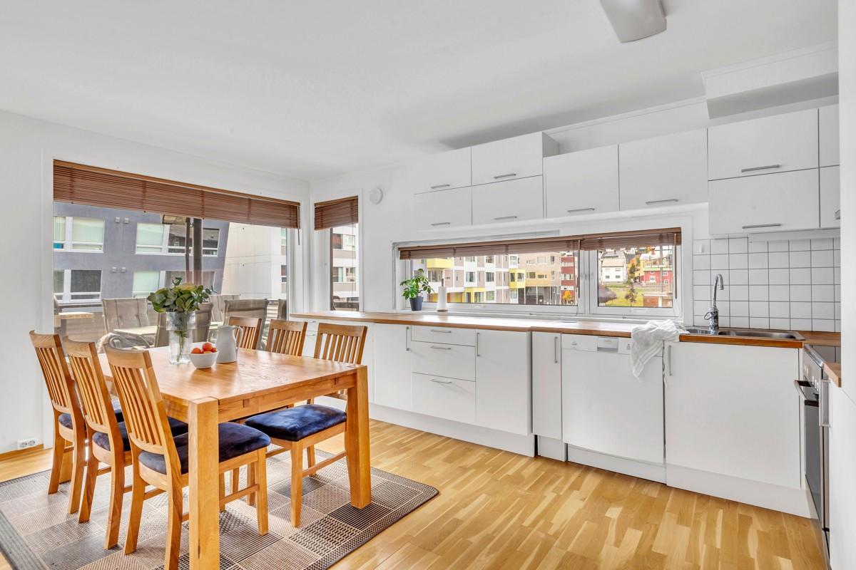 Kjøkkeninnredning med hvite glatte fronter og heltre benkeplate