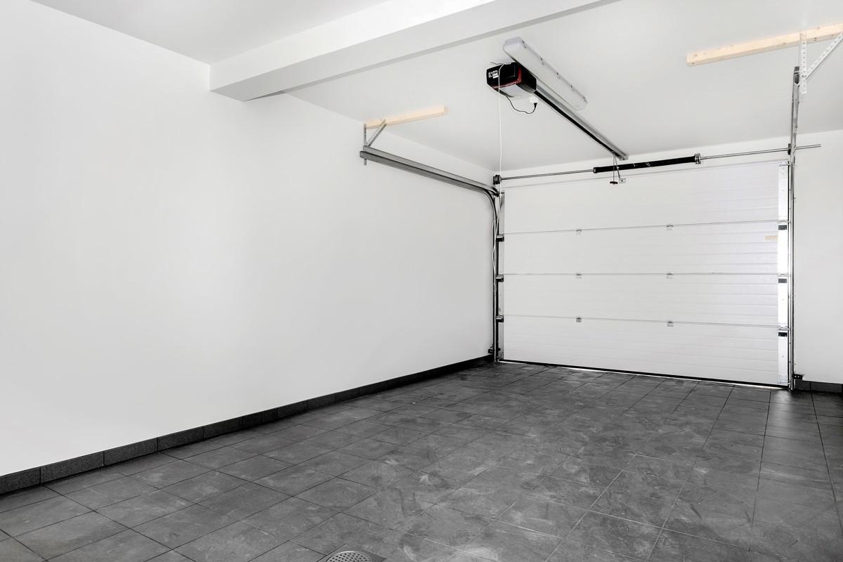 Flislagt integrert garasje med fjernstyrt åpner til garasjeport og strøm til el-bilader