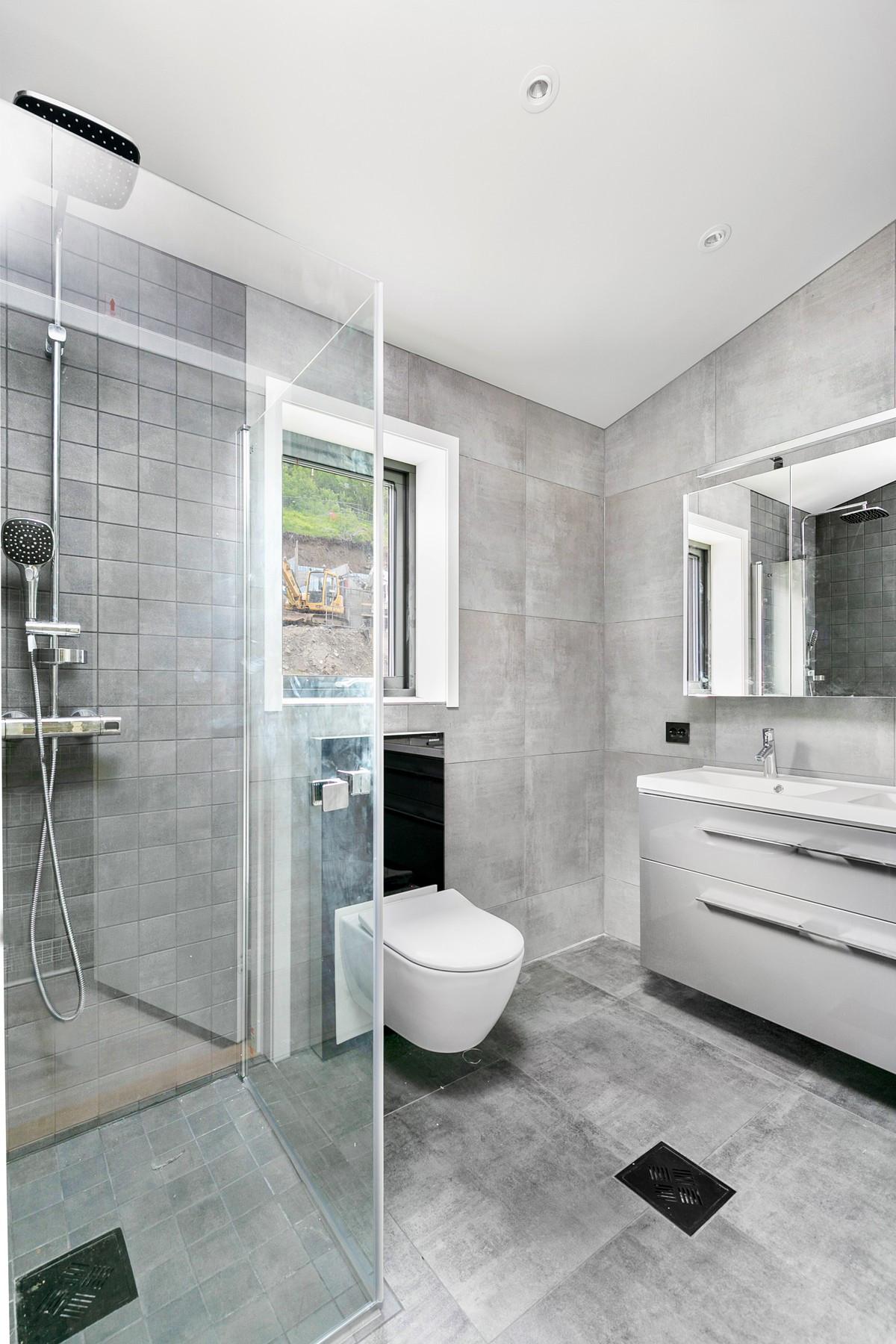 """Bad tilknyttet hovedsoverom er komplett flislagt med gulvarme og moderne innredet med dobbelvask og ledlys i skap og speil, samt dusj med """"waterfall"""""""