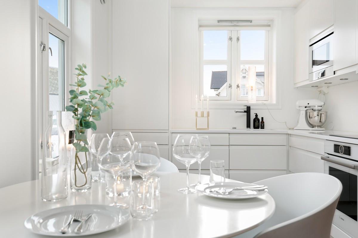 Lyst og innholdsrikt kjøkken med integrerte hvitevarer