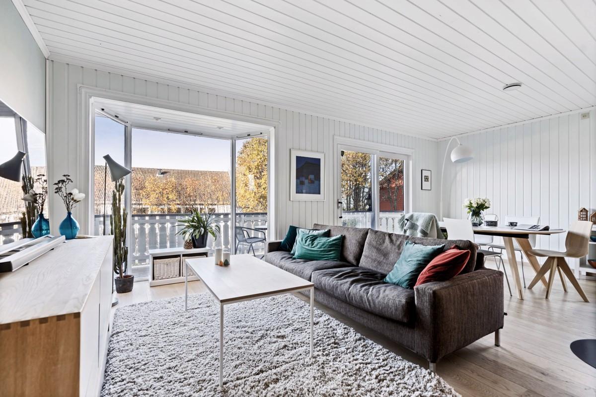 Fin stue med parkett på gulv og rikelig med innslipp av lys fra store vindusflater
