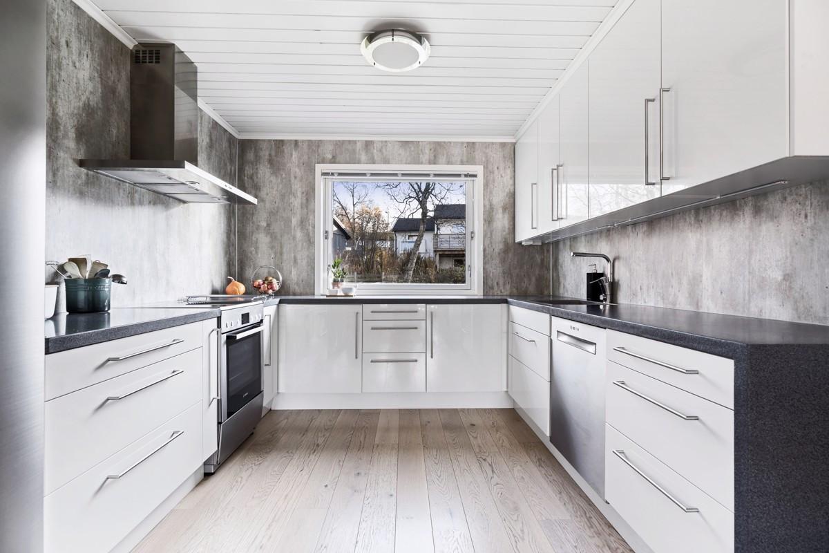 Elegant og romslig kjøkken med hvite glatte fronter og integrerte hvitevarer