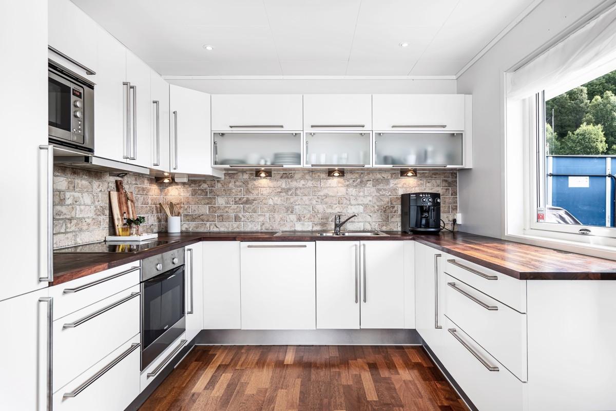 Kjøkken med fliser over heltre merbau benkeplate og integrerte hvitevarer