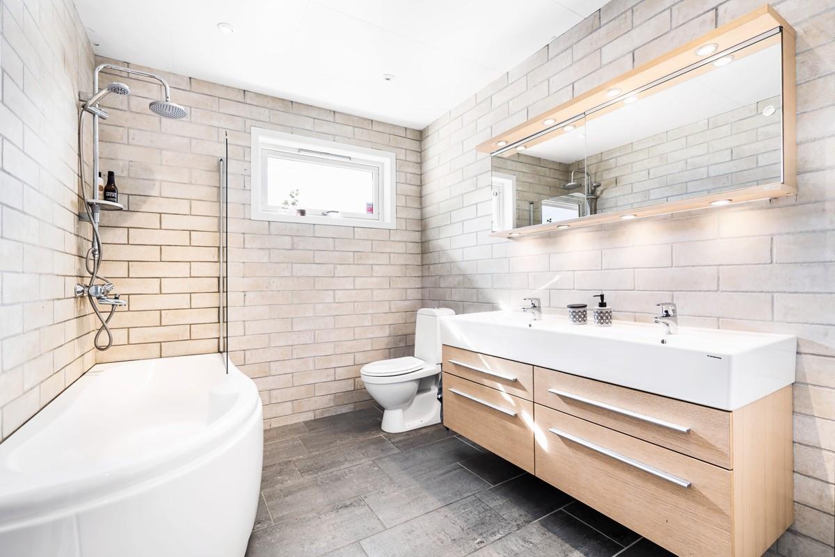 Lekkert flislagt bad med gulvvarme og badekar