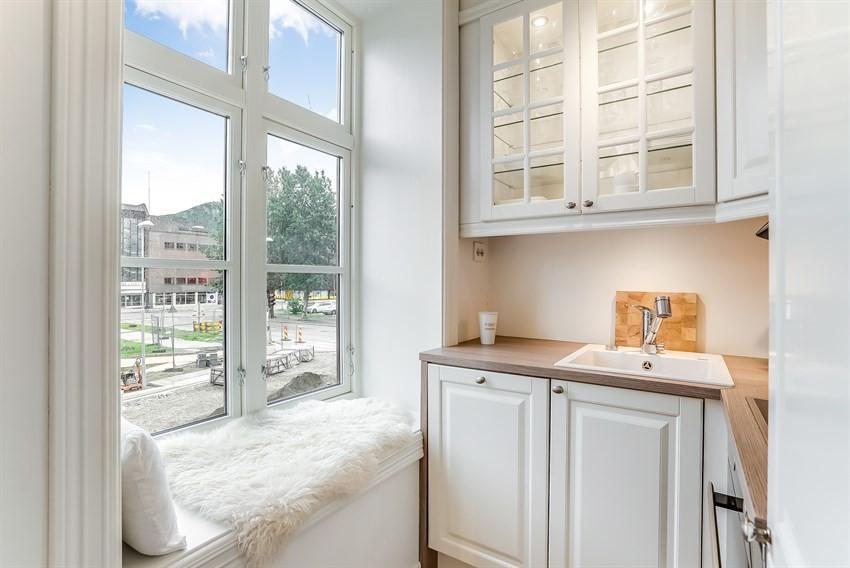 Kjøkken med stort vindu som innbyr til en rolig stund