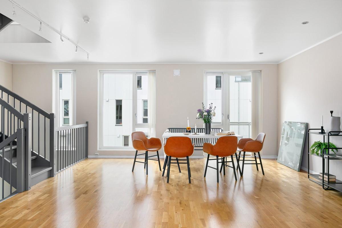 Den romslige stue/kjøkken-løsningen har lyse flater og gjennomgående lysinnslipp
