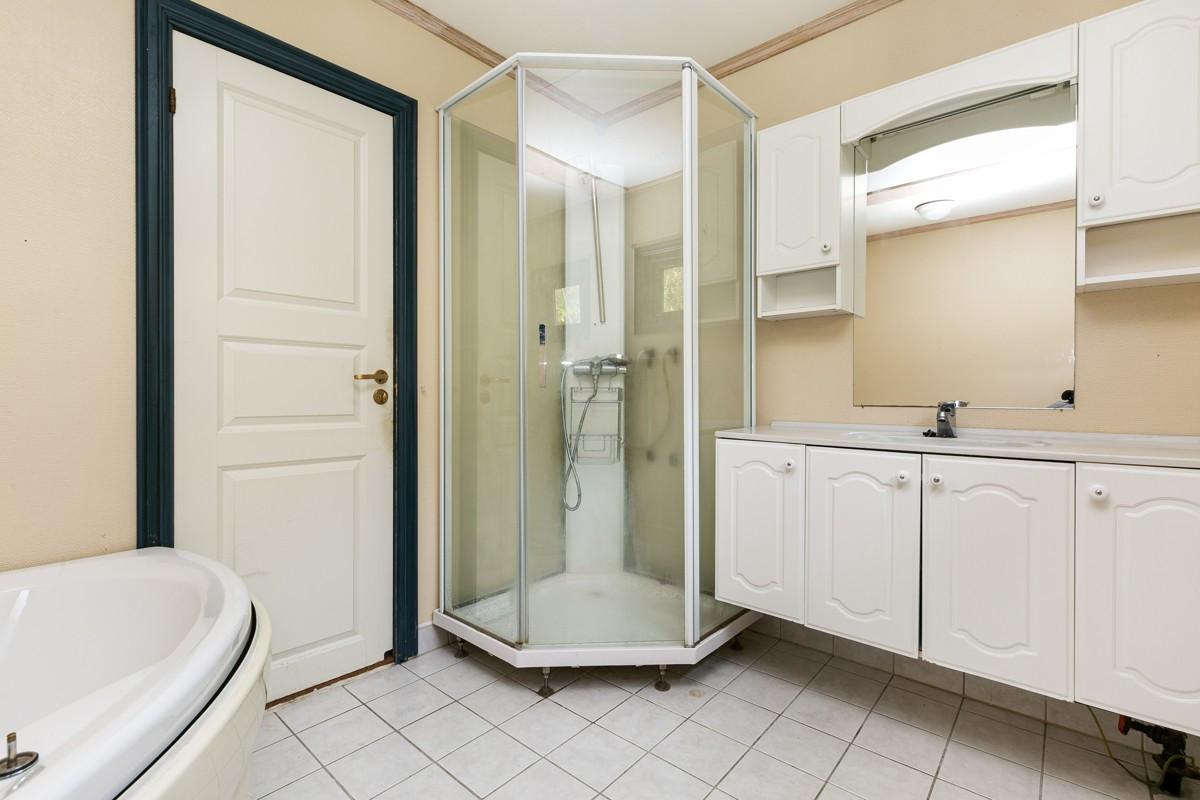 Bad med dusjkabinett og badekar, samt varme i gulv