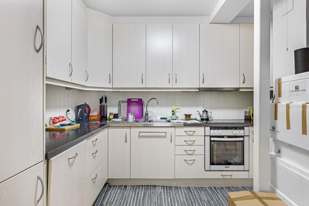 Kjøkken med integrerte hvitevarer og rikelig med oppbevaringsplass i skap og skuffer