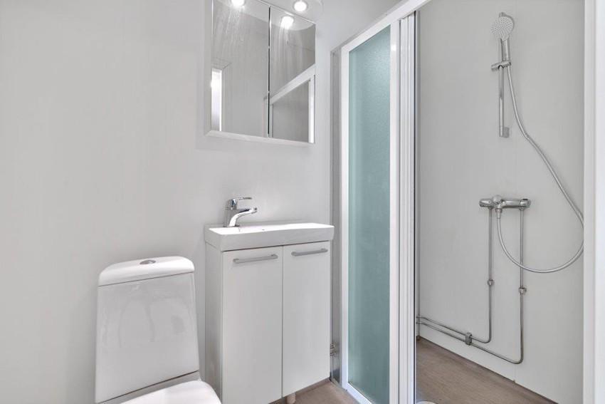 Baderom med toalett, baderomsinnredning og dusjhjørne
