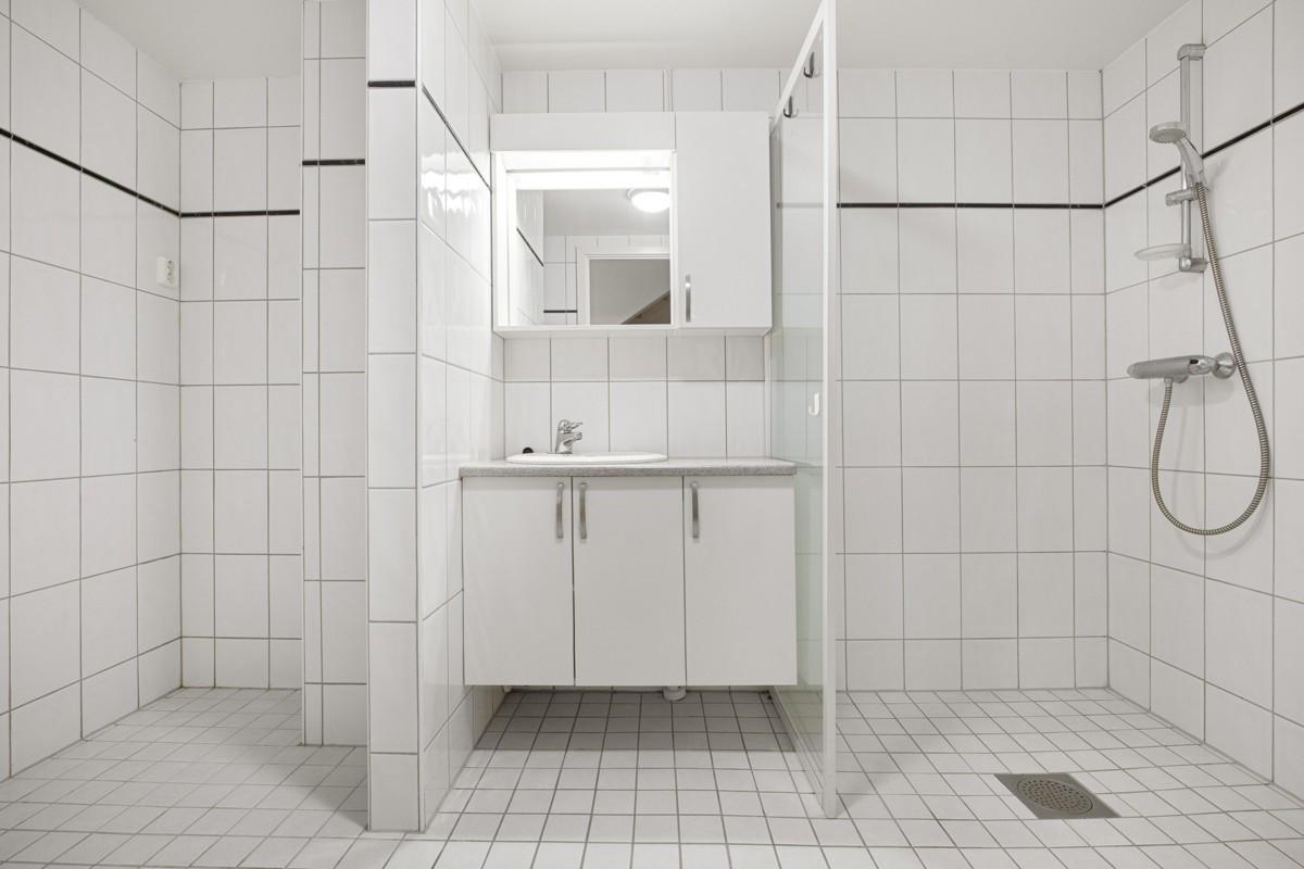 Komplett fliselagt baderom med dusjnisje og baderomsinnredning