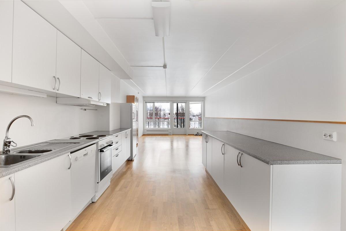 Kjøkkeninnredning med hvite glatte fronter. Stor benkeplass, samt gode oppbevaringsmuligheter i over- og underskap
