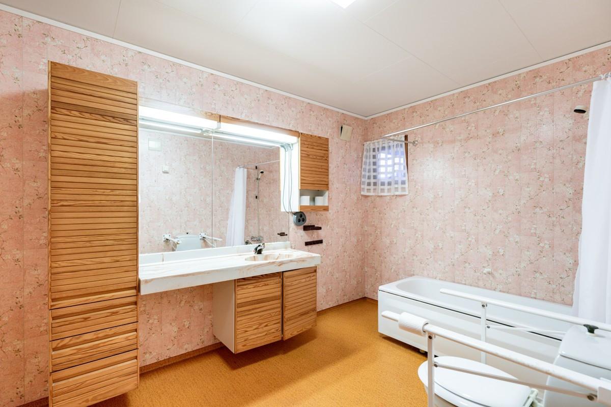 Bad innredet med badekar og opplegg til vaskemaskin
