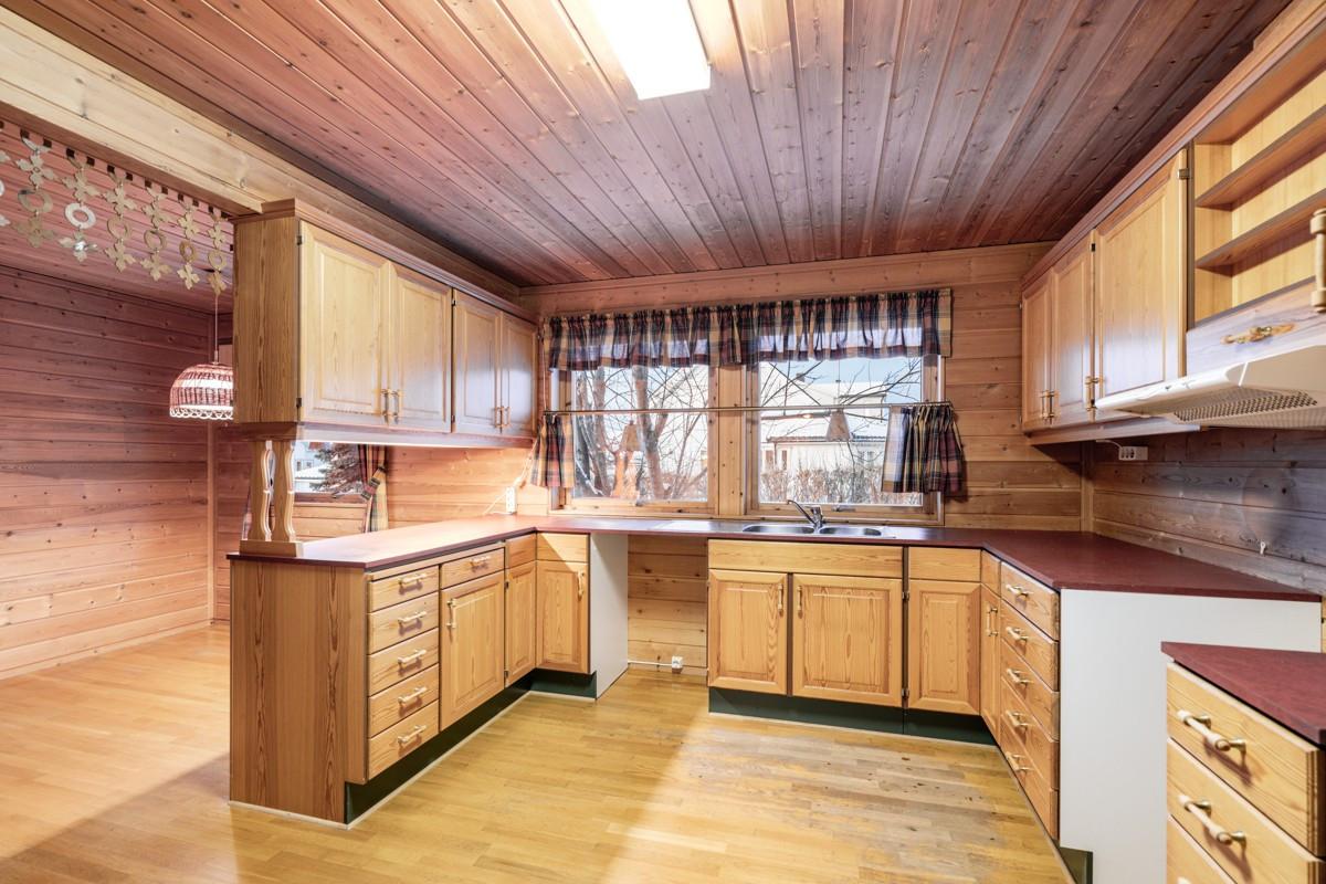 Kjøkken med fin innredning i furu og opplegg til oppvaskmaskin
